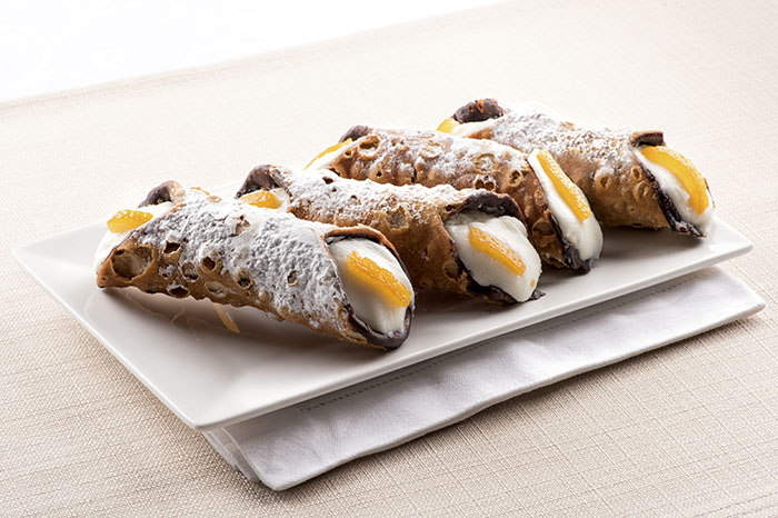 Four cannoli Sicilia, or Sicilian cannoli, deep fried pastry tubes with a sweet ricotta filling garnished with colorful orange rind and served on a rectangular plate